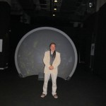 Rainer Maria Latzke in front of a parabolic projector screen